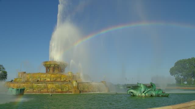 a rainbow arcs across buckingham fountain in chicago's grant park. - buckingham fountain stock videos and b-roll footage