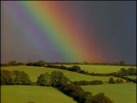 rainbow breaking through grey sky patchwork green fields below bordered by trees - escapism stock videos & royalty-free footage
