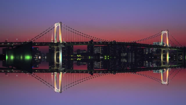 Rainbow Bridge at dusk mirroring in water - Tokyo, Japan