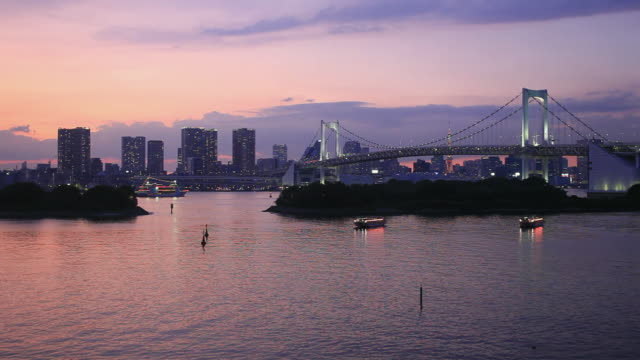 ws ha rainbow bridge at dusk, skyline in background / minato, tokyo, japan - tokyo bay stock videos and b-roll footage