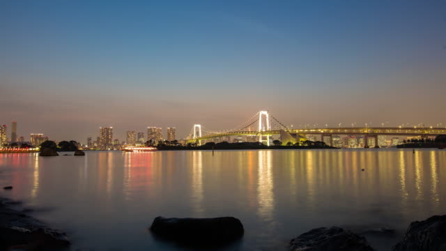 t/l 8k rainbow bridge in tokyo at sunset - sunset to night time lapse stock videos & royalty-free footage