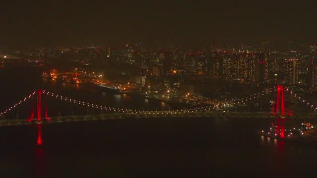 aerial, rainbow bridge lit up red, tokyo, japan - minato ward stock videos & royalty-free footage