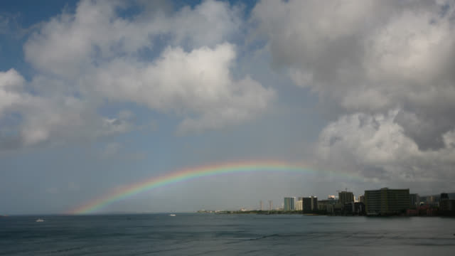time lapse long shot rainbow, clouds and rain over waikiki hotels on beach and ocean - 天気点の映像素材/bロール