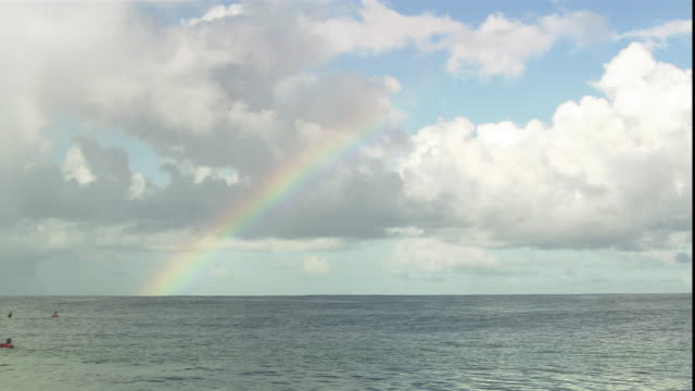 a rainbow fades into the clouds over the ocean as surfers wait for approaching waves. - south pacific ocean stock videos & royalty-free footage