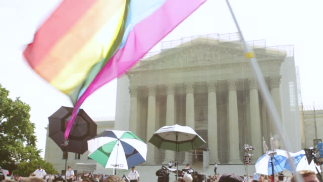 ws la rainbow flag is waving in front of supreme court building during rally for marriage equality / washington, district of columbia, united states - oberstes bundesgericht der usa stock-videos und b-roll-filmmaterial