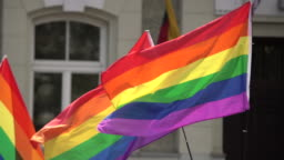 Rainbow flag supporting LGBT community on gay parade event. Colourful flag in the crowd during gay pride celebration