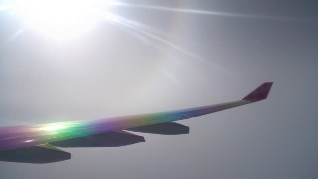 rainbow flight view taken from airplane window view with aircraft wing and sun light - mack2happy stock videos and b-roll footage