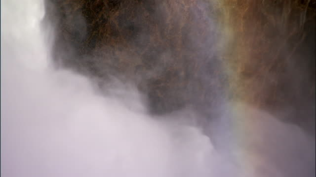vídeos de stock, filmes e b-roll de rainbow formed in swurling spray from lower yellowstone falls, yellowstone, usa - arco íris