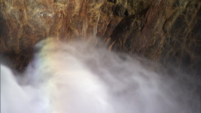 rainbow formed in swurling spray from lower yellowstone falls, yellowstone, usa - lower yellowstone falls stock videos & royalty-free footage