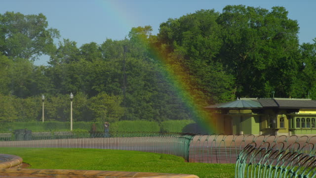 a rainbow forms in the mist from buckingham fountain in grant park, chicago, illinois. - buckingham fountain stock videos & royalty-free footage