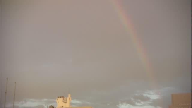 a rainbow glows in a dusky sky. - 虹点の映像素材/bロール