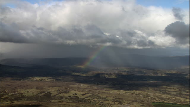 a rainbow glows underneath clouds floating above a hilly landscape. - scotland stock videos & royalty-free footage