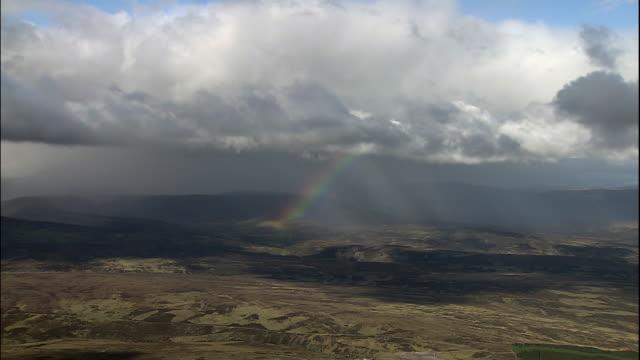 a rainbow glows underneath clouds floating above a hilly landscape. - skottland bildbanksvideor och videomaterial från bakom kulisserna