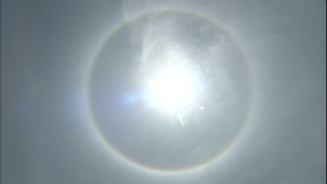 a rainbow halo glows around the sun. - halo stock videos and b-roll footage