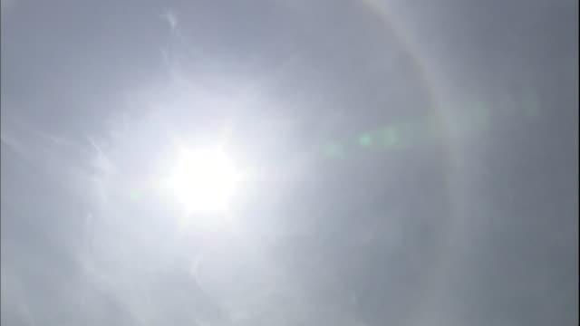 a rainbow halo glows around the sun. - spectrum stock videos & royalty-free footage