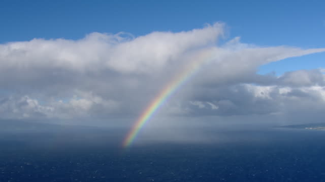 a rainbow hangs between clouds and the blue waters of the pacific ocean. - 虹点の映像素材/bロール