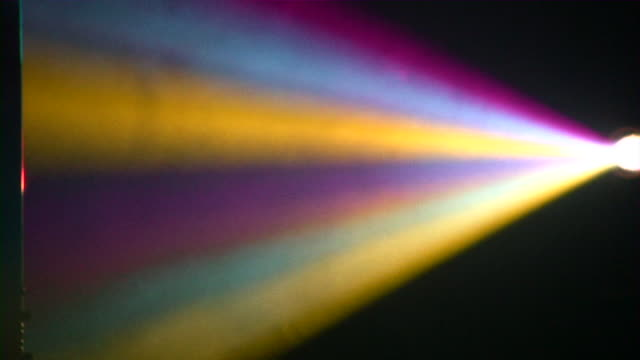 Rainbow light beams from a prism on black background