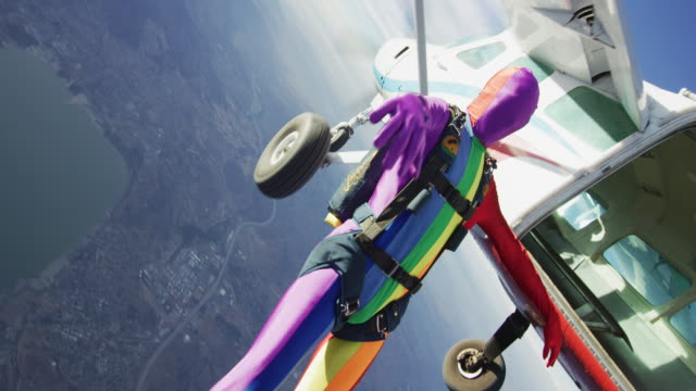 rainbow morph suit skydiver exits plane - lesbe lesben stock-videos und b-roll-filmmaterial