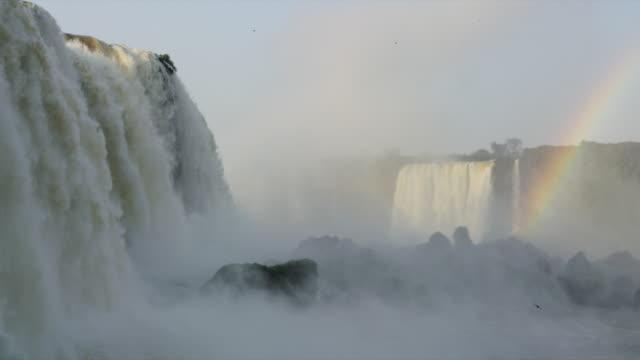 Rainbow over Iguazu Falls as birds fly over the mist