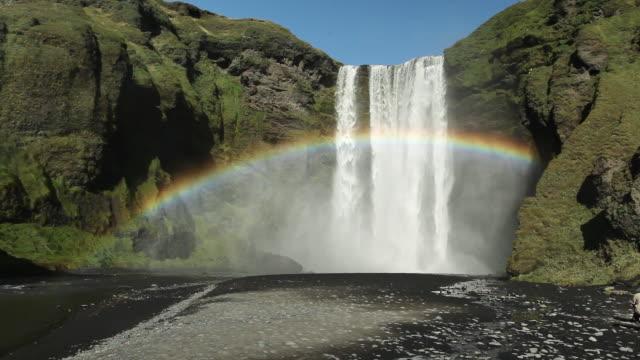 ms rainbow over luch skogafoss waterfall, black volcanic sand surrounds area / hof, vestur-skaftafellssysla, iceland - rainbow stock videos & royalty-free footage