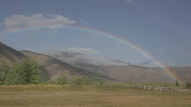 rainbow over mountain meadow - 虹点の映像素材/bロール