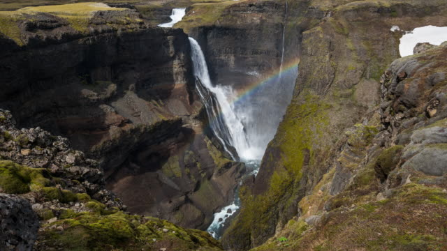 Rainbow over waterfall dropping down into canyon
