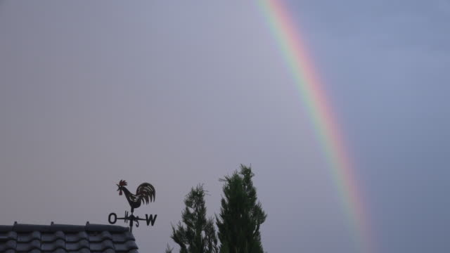 Rainbow over weather vane