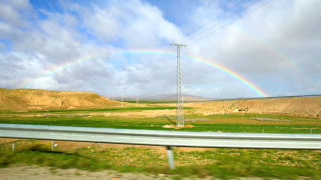 vídeos de stock, filmes e b-roll de rainbow seen from car window while driving in morocco - arco íris