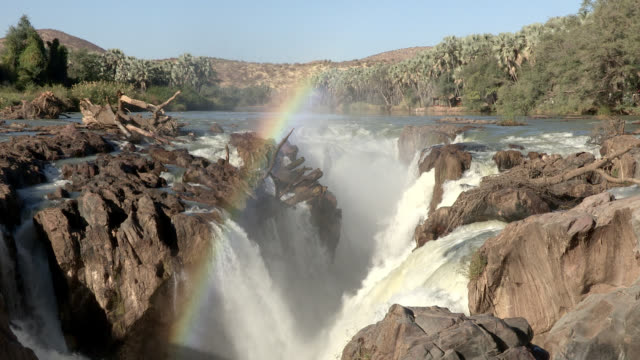 A rainbow shines in the misty water from the Epupa Falls on the Kunene River.