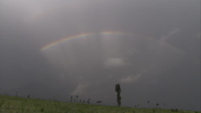 a rainbow stretches over a hillside. available in hd. - hd format stock videos & royalty-free footage