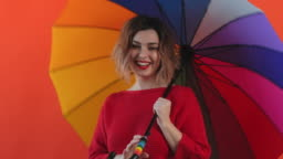 Rainbow umbrella. Portrait of happy smiling young sexy girl rotating rainbow umbrella in red sweater on red background slow motion. Pleasure. Emotions of people. Monotone. Copy space