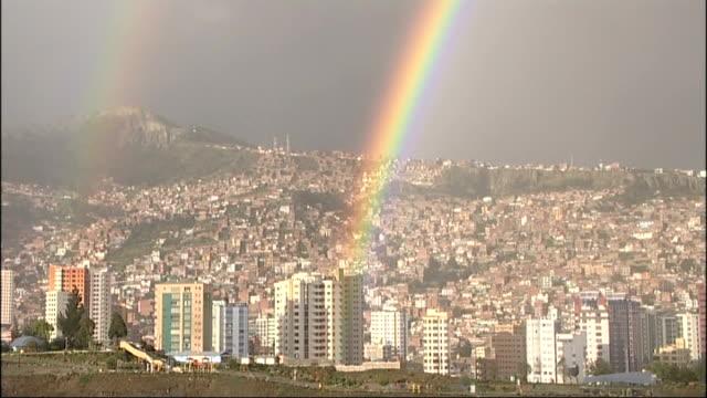 rainbows over la paz / silver tin mining at potosi / general views potosi bolivia la paz striking high angle long shots of rainbows arching over city... - bolivien stock-videos und b-roll-filmmaterial