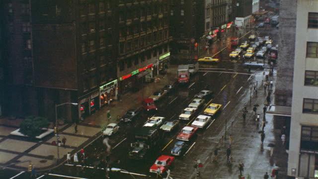 1969 ha ws rain-drenched city street with traffic and pedestrians / manhattan, new york - 1969 bildbanksvideor och videomaterial från bakom kulisserna