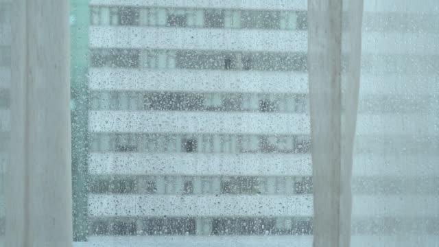 regentropfen klopfen am fenster - fensterfront stock-videos und b-roll-filmmaterial