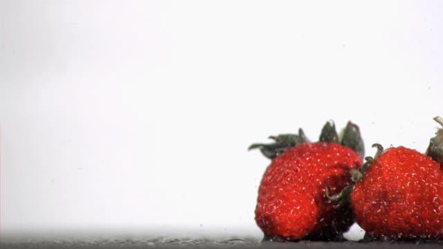 vídeos de stock, filmes e b-roll de raindrops falling in super slow motion on fruits - quatro objetos