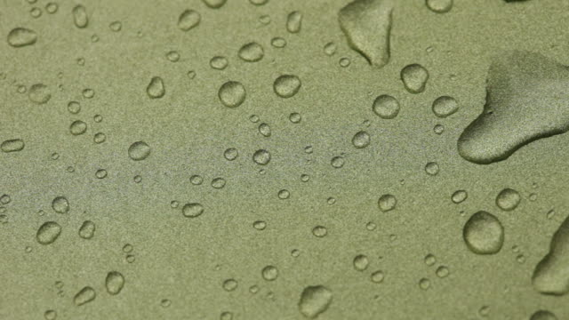 Raindrops Falling Onto Gold Metallic Surface and Flowing Down
