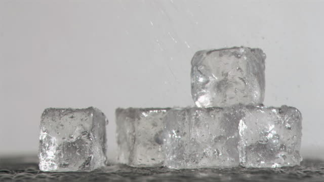 Raindrops in super slow motion falling on ice cubes
