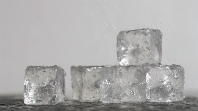 vidéos et rushes de raindrops in super slow motion falling on ice cubes - glaçon