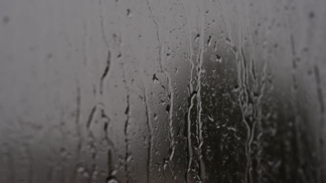 raindrops on window. water drops and streams flow down the glass. - rain stock videos & royalty-free footage