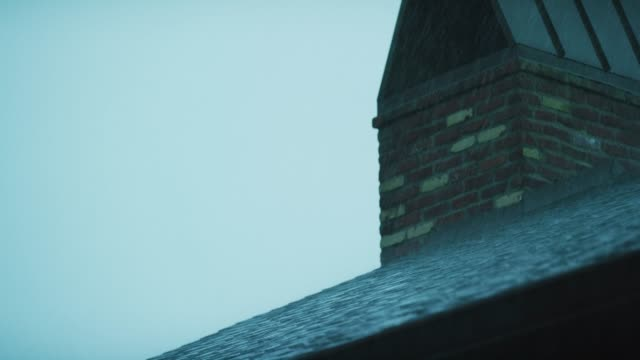 raindrops splash against rooftop shingles and a brick chimney during a storm - gutter stock videos and b-roll footage