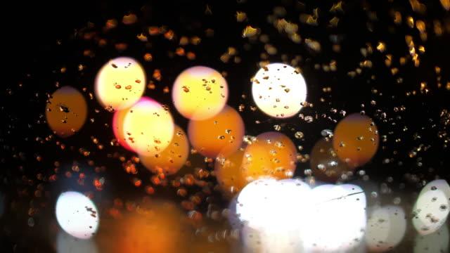 vidéos et rushes de gouttes de pluie avec le fond de bokeh léger de cercle sur la voiture dans le jour d'embouteillage - pare brise
