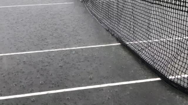 vidéos et rushes de il pleut sur un court de tennis - ball