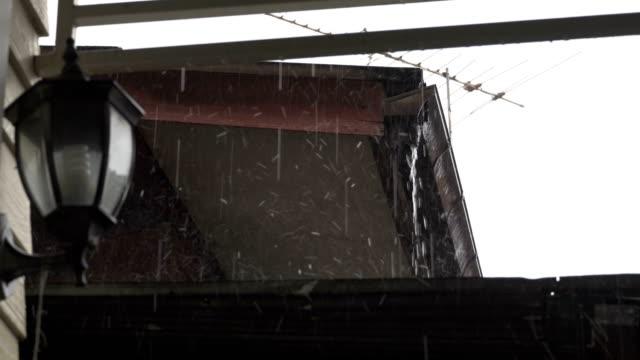 屋外ランプの横の屋根の外で雨 - 電灯点の映像素材/bロール
