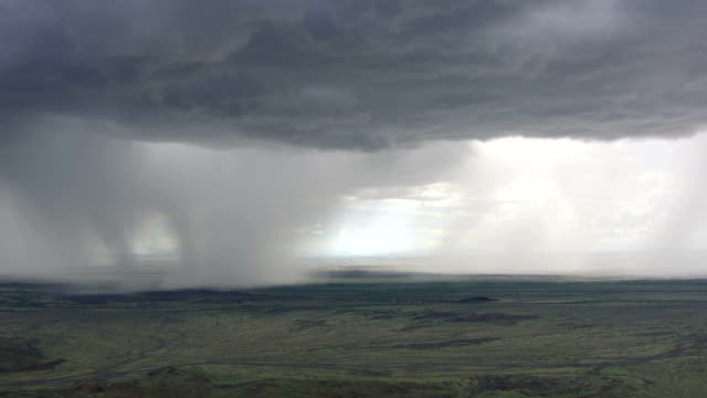 ws aerial raining storm clouds over landscape / kenya - storm cloud stock videos & royalty-free footage