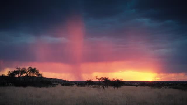 vídeos y material grabado en eventos de stock de a rainstorm streaks a glowing pink and purple sky over a desert plain. available in hd. - desierto del kalahari