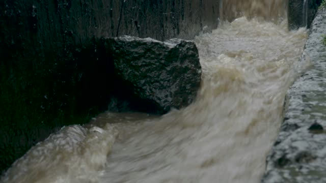 rainwater gushing into a gutter on a road in free town, sierra leone, west africa. - sidewalk gutter stock videos & royalty-free footage