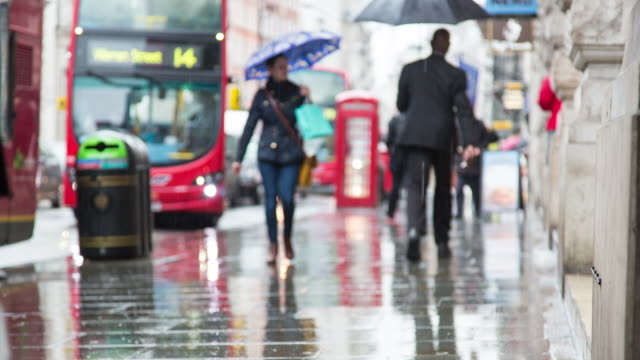 Rainy afternoon time lapse of foot traffic along Piccadilly, with iconic London imagery including a red telephone box and London buses and black cabs