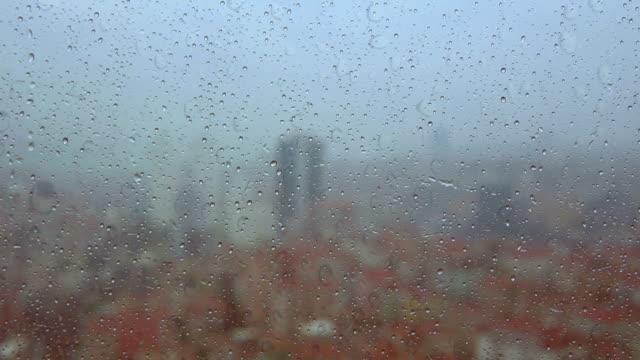 vidéos et rushes de ville de pluie - gouttes de pluie sur la fenêtre - ville en arrière-plan - lieu d'habitation