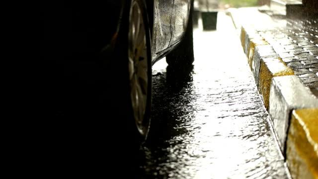 Verregneter Tag in den Straßen der Stadt, Wassertropfen, Pfützen, Auto vorbei, super Zeitlupe, geringe Tiefenschärfe.