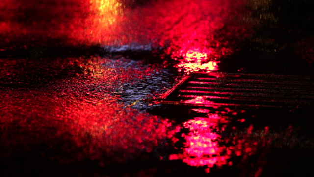 vidéos et rushes de rainy day on a colorful street with traffic - macadam